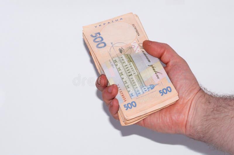 Pengar i den manliga handen p? en vit bakgrund, ukrainsk hryvnia per den stora packen av r?kningar, n?rbild, kopieringsutrymme royaltyfri foto