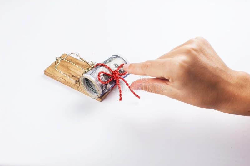 Pengar i en råttfälla med en hand På en vit bakgrund fälla för mus för pengar för kvinnaförsöktagande arkivfoton