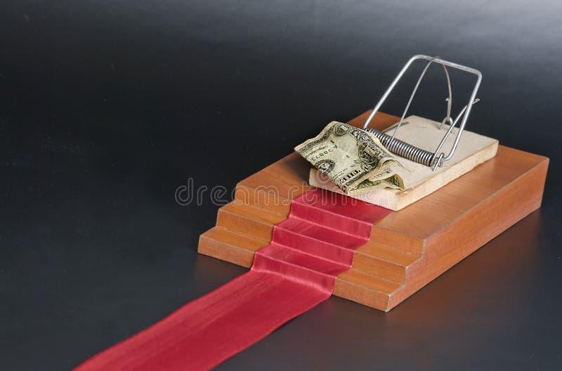 Pengar i en råttfälla på den röda mattan och svartbakgrunden arkivbilder