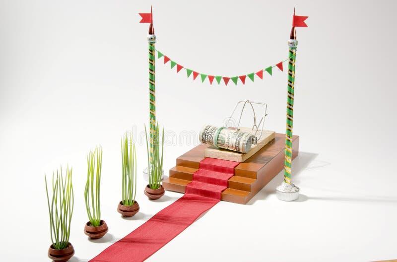 Pengar i en råttfälla på den röda mattan och vitbakgrunden arkivfoto