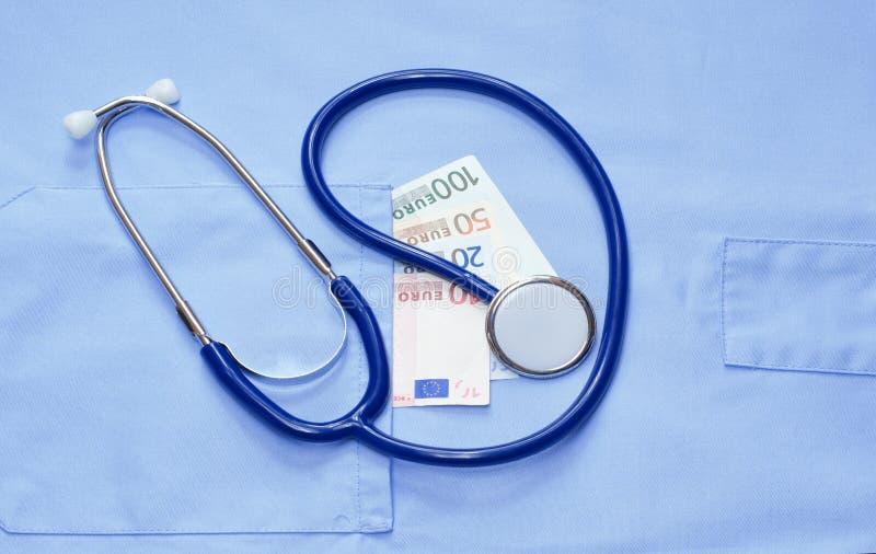 Pengar i facket av en medicinsk likformig och stetoskop royaltyfri bild