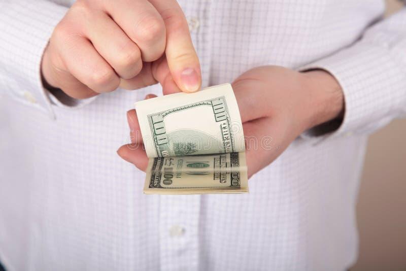 Pengar i händer arkivbild