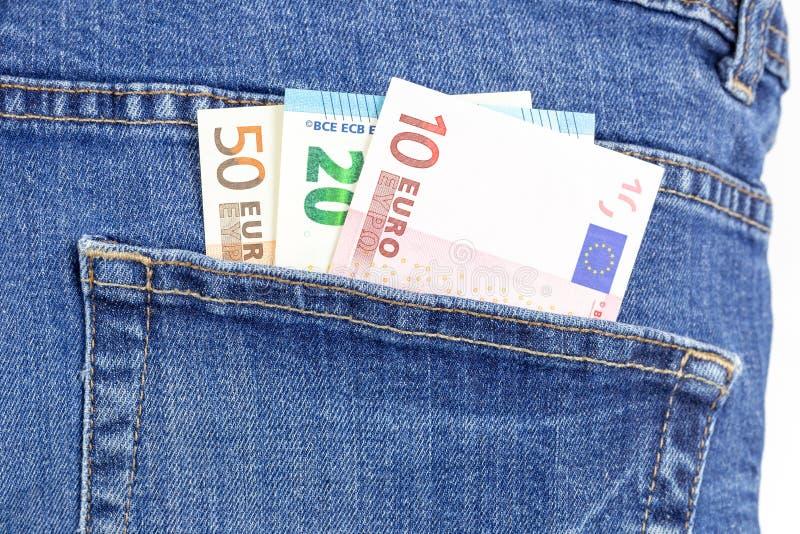 Pengar i jeansen stoppa i fickan Foto för eurovalutamakro arkivfoto