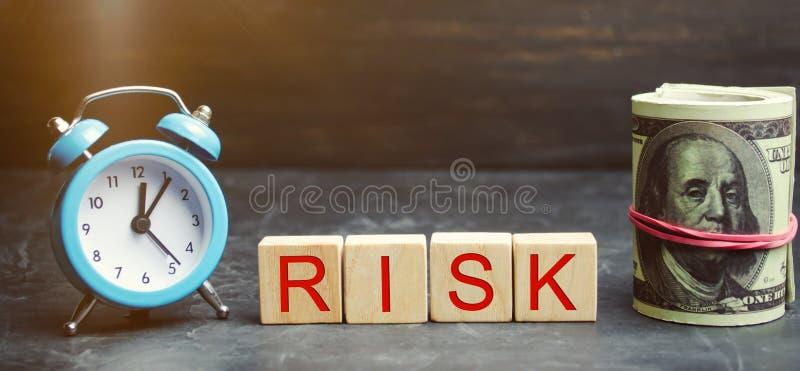 Pengar, klocka och träkvarter med ordrisken Begreppet av den finansiella risken Befogade risker Investera i ett affärsprojekt royaltyfri foto