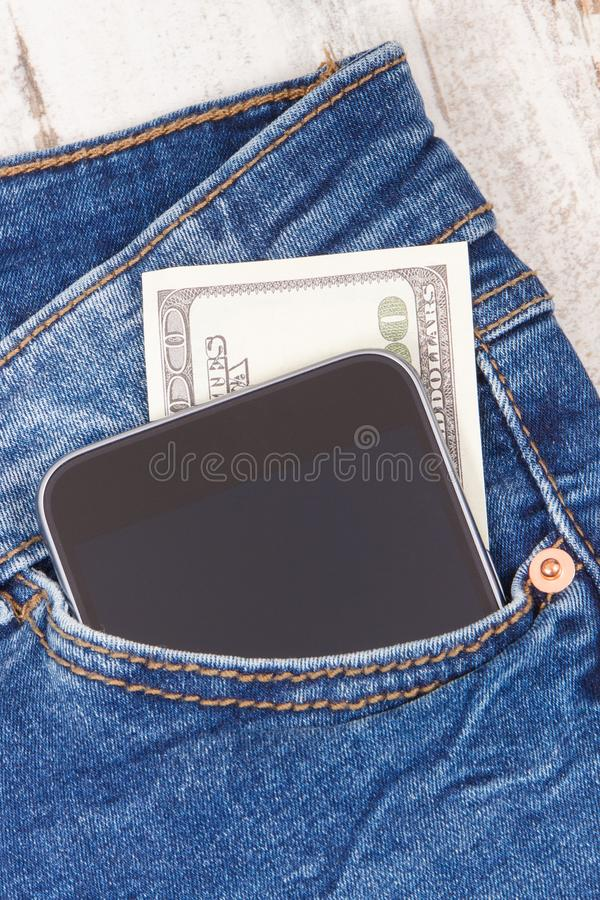 Pengar med mobiltelefonen i jeans stoppa i fickan Cashless betala f?r att shoppa begrepp royaltyfri fotografi