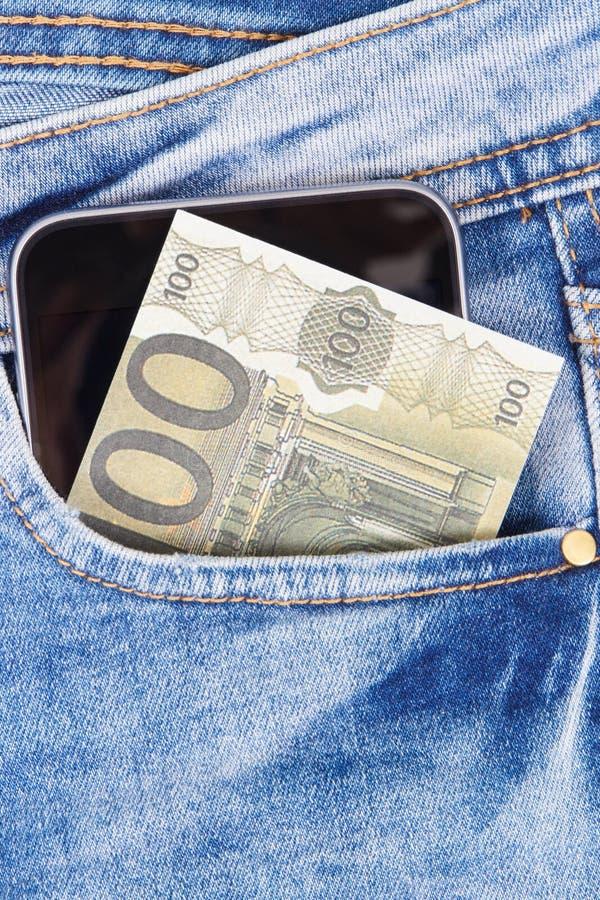 Pengar med mobiltelefonen i jeans stoppa i fickan Cashless eller kassa som betalar f?r att shoppa begrepp royaltyfria bilder