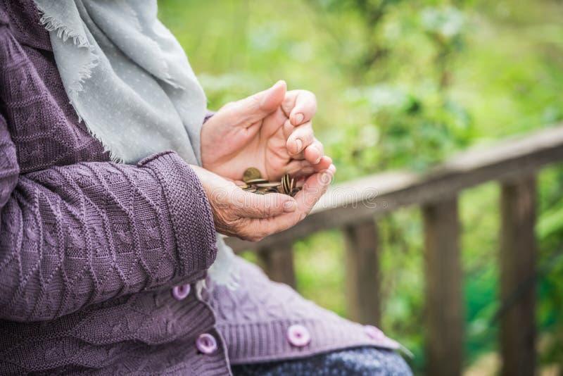 Pengar, mynt, farmodern på pensioner och ett begrepp av en bosatt minimi - i händer av isn-`en t för gammal kvinna nog pengar arkivfoton
