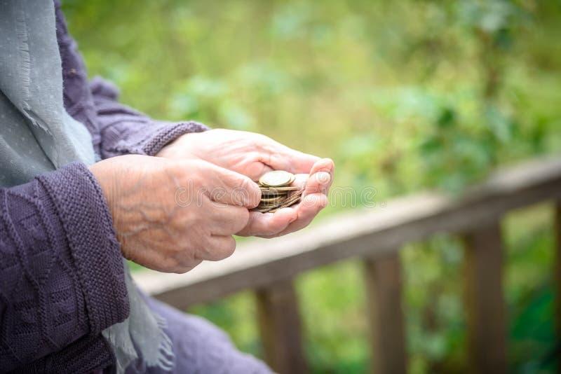 Pengar, mynt, farmodern på pensioner och ett begrepp av en bosatt minimi - i händer av isn-`en t för gammal kvinna nog pengar royaltyfri bild
