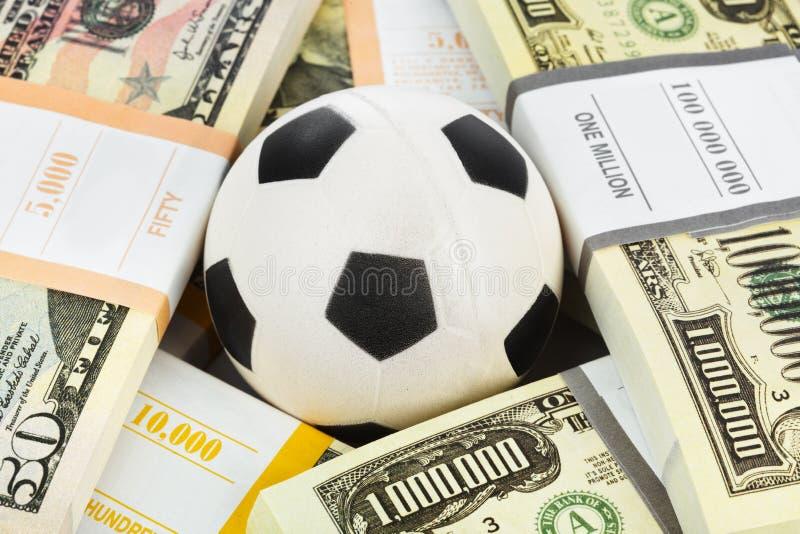 Pengar och fotbollboll royaltyfria foton