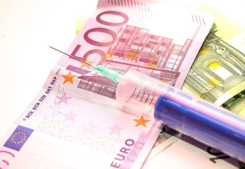 Pengar och injektionsspruta royaltyfria bilder
