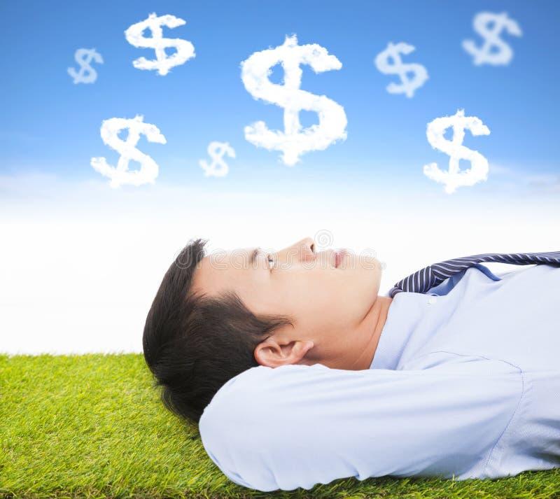 Pengar och mål för affärsman tänkande på en äng arkivbild