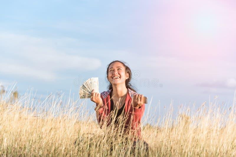 Pengar och mobiltelefoner för lycklig flicka hållande arkivbild