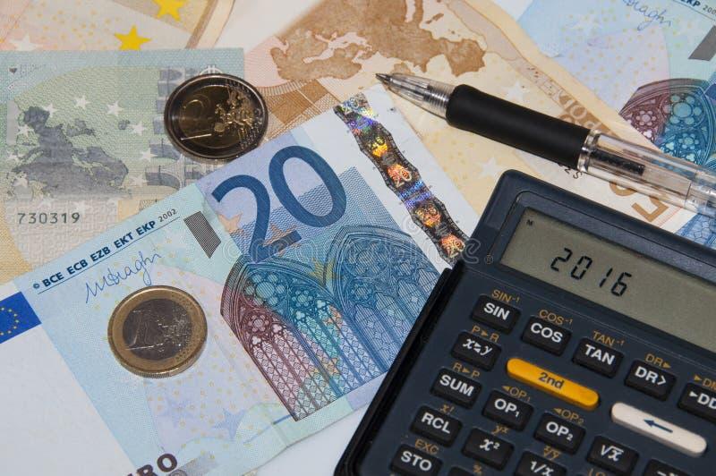 Pengar och räknemaskin och penna i året 2016 royaltyfria foton