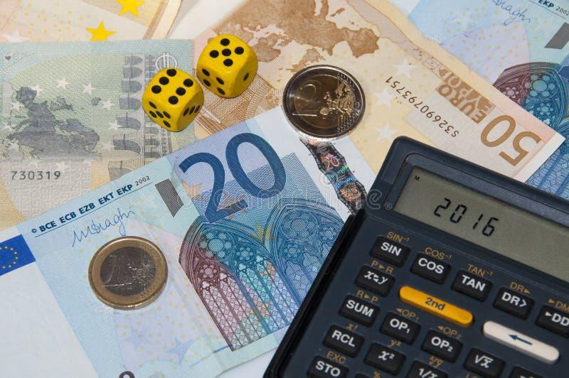 Pengar och räknemaskin och tärning i året 2016 arkivbilder
