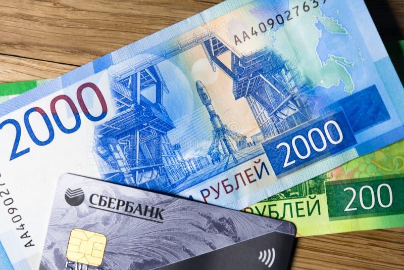 Pengar- och sberbankkreditkort på en träig bakgrund arkivfoto