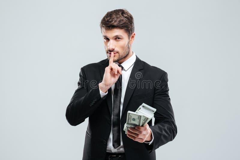 Pengar och visningen för stilig ung affärsman tystar hållande tecknet royaltyfri foto
