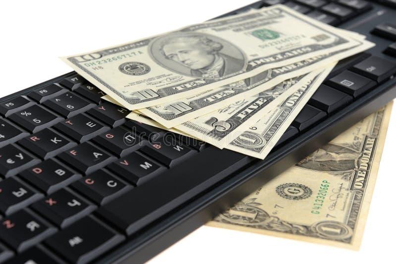 Pengar på det svarta tangentbordet som isoleras på vit arkivfoton
