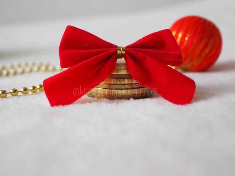 Pengar som julgåvan, mynt på en snö med den röda pilbågen royaltyfri fotografi