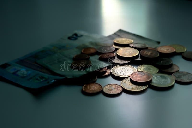 Pengar sover aldrig Kassa på månsken, eurosedlar och mynt på tabellen M?rk aff?rsid? royaltyfria bilder