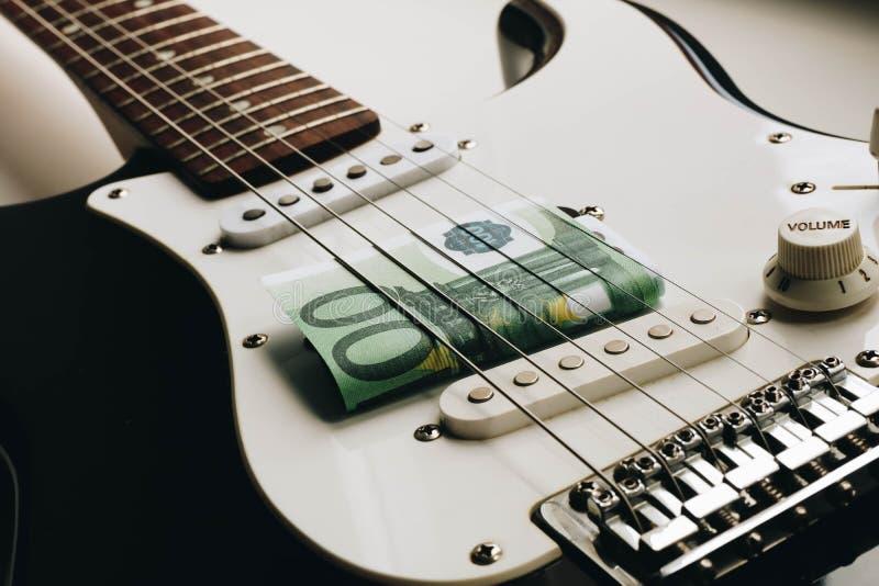 Pengar under raderna av en gitarr Hundra euro under raderna av en gitarr royaltyfria bilder