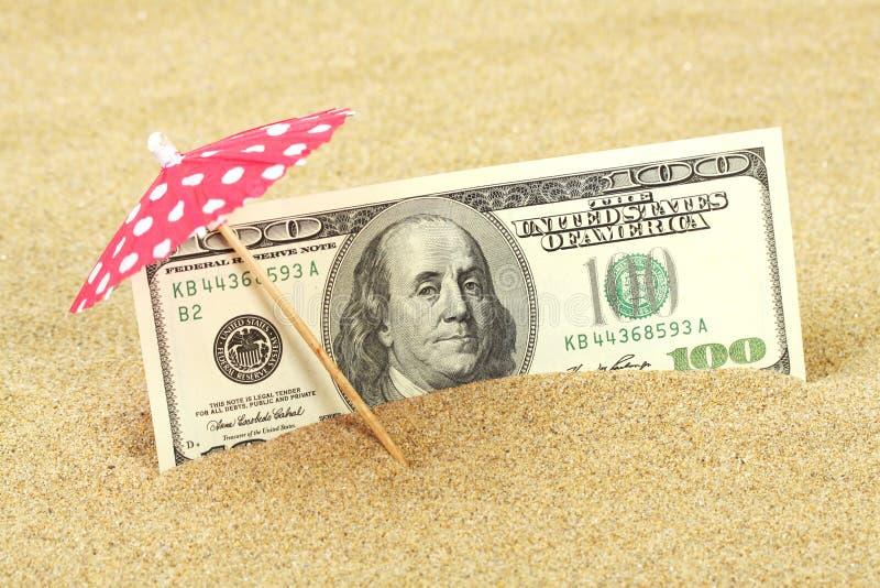 Pengaramerikanen hundra dollarräkningar i strandsanden under rött och vit pricker parasollen arkivbild