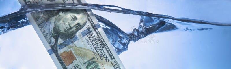 Pengarbegrepp som visar US dollar som sjunker i vatten som ett symbol av arkivbilder
