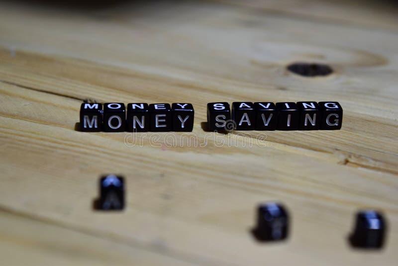 Pengarbesparingmeddelande som är skriftligt på träkvarter royaltyfri foto