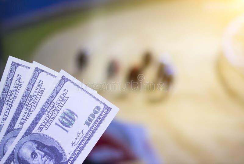 Pengardollar på bakgrunden av en TV på som show ett hundlopp, sportar som slå vad, dollar arkivfoton