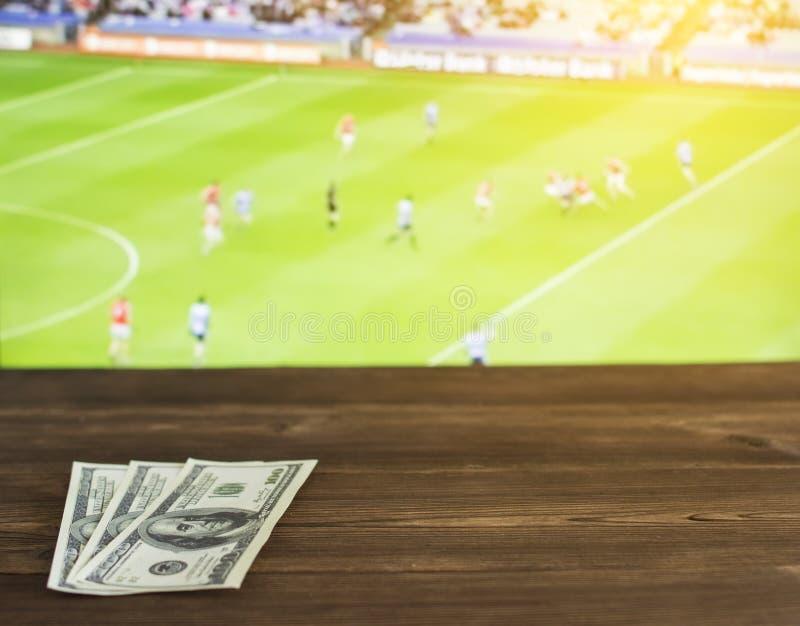 Pengardollar på bakgrunden av TV:N på som ersisk fotboll för show, sportar som slå vad, dollar, Gaelic Football royaltyfria foton