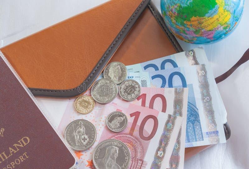 Pengareurosedlar, mynt, jordklot, plånbok och pass royaltyfria bilder