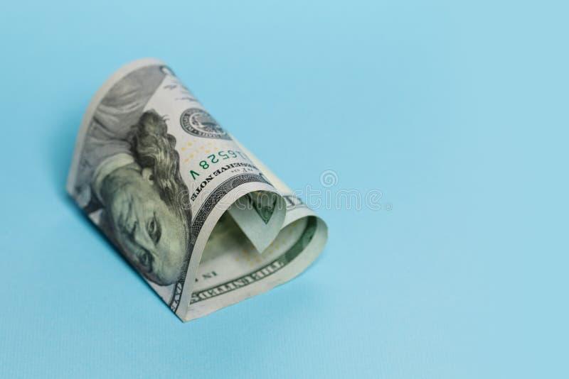 Pengargåva och kommersiellt begrepp för pengarinvesteringvinst För anmärkningshjärta för US dollar 100 form på tom blå bakgrund royaltyfria bilder