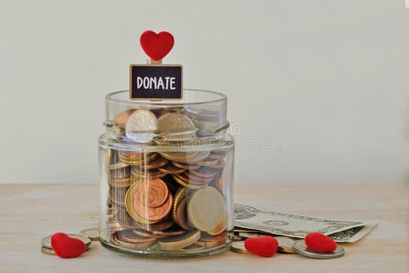 Pengarkruset av mynt med donerar mycket etiketten och hjärtor - välgörenhetbegrepp royaltyfria foton