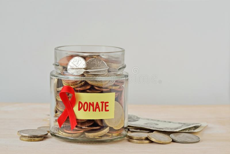Pengarkruset mycket av mynt med det röda bandet och att donera etiketten - bistår välgörenhet och forskningsfondbegrepp arkivbilder