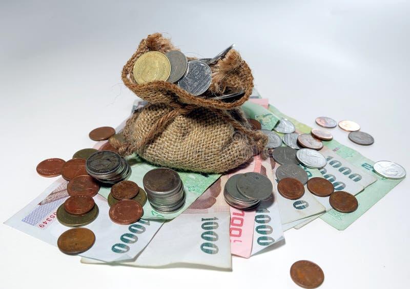 Pengarmynt kom ut från brun pengarpåse royaltyfri bild