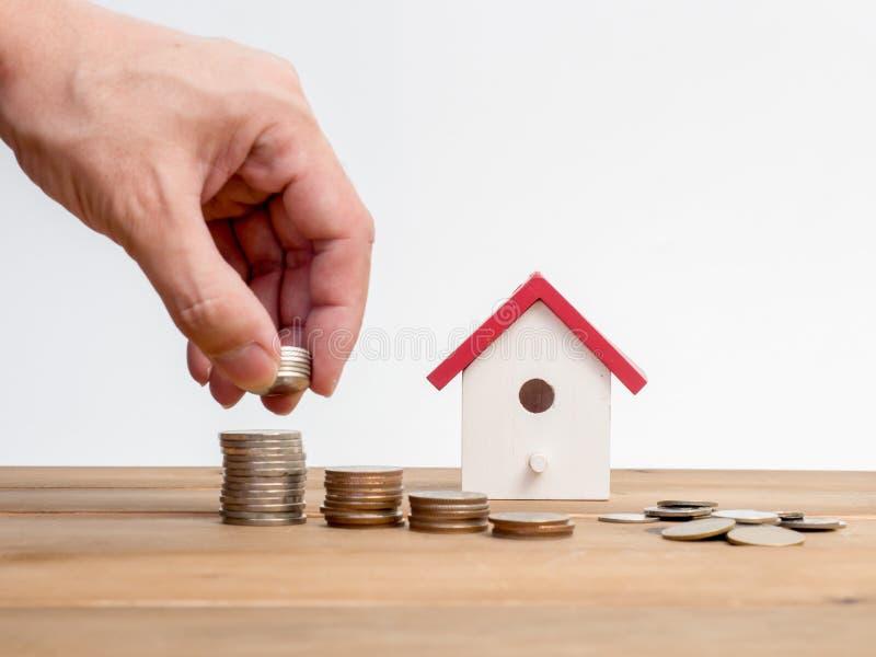 Pengarmynt staplar att växa med det röda huset på wood bakgrund Affärstillväxtinvestering och finansiella begreppsidéer Fastighet arkivbilder