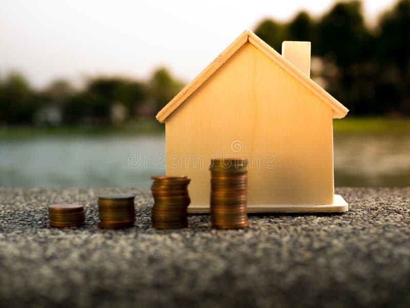 Pengarmynt staplar att växa med husbakgrund som sparar pengar för hem- begrepp royaltyfri fotografi