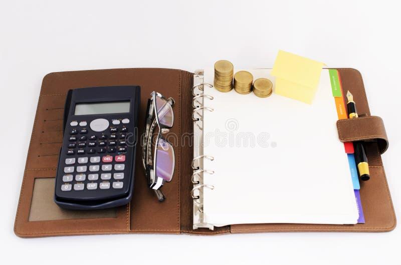 Pengarmyntbunt och gult pappers- hus och räknemaskin och glasögon och reservoarpenna fotografering för bildbyråer
