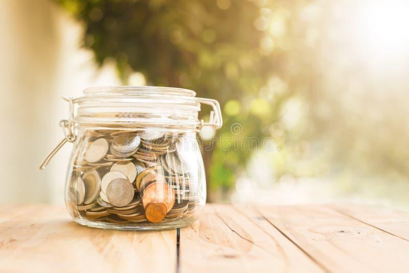 Pengarmyntinsättningen av sparar pengar för förbereder sig royaltyfri fotografi