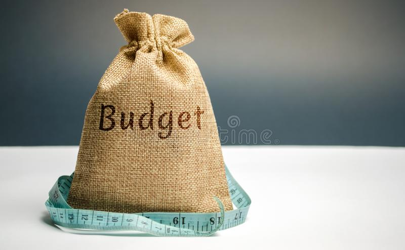Pengarpåse med den ordbudgeten och måttbandet Begreppet av inskränkt vinst Brist av pengar och armod Liten inkomst lön royaltyfri foto
