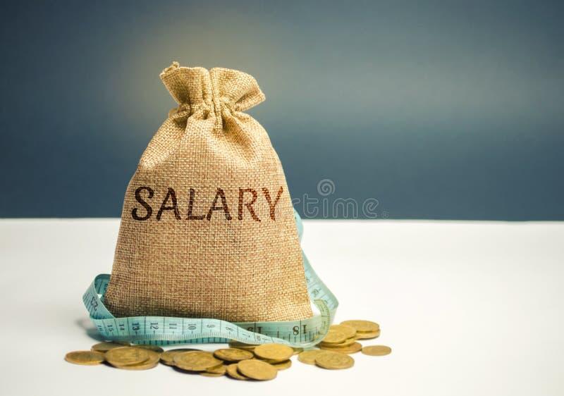 Pengarpåse med den ordlönen och måttbandet timpenningsnitt Begreppet av inskränkt vinst Brist av pengar och armod Liten inkomst arkivfoto