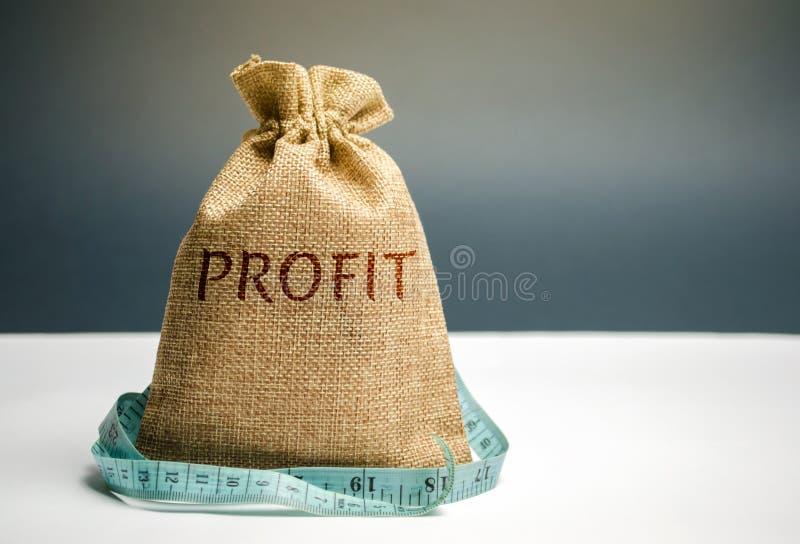 Pengarpåse med den ordvinsten och måttbandet Begreppet av inskränkt vinst Brist av pengar och armod Liten inkomst lön arkivbilder