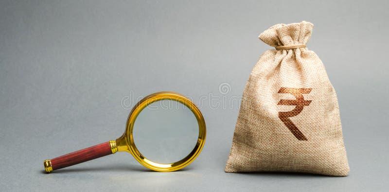 Pengarpåse med det rupierupiahtecknet och förstoringsglaset Begreppet av att finna k?llor av investeringen och sponsorer medm?nsk royaltyfri fotografi