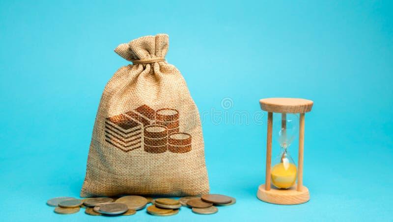 Pengarpåse med mynt och en klocka/ett timglas Tid ledning och fördelning bondsr?knemaskinen kan ?ndra pengar f?r inskrifter f?r k royaltyfria foton