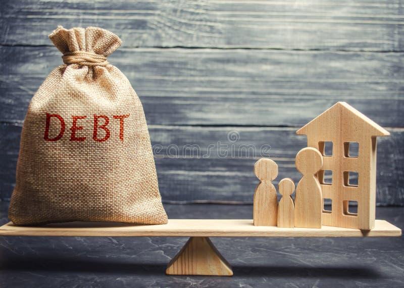 Pengarpåse med ordskulden och ett miniatyrhus med en familj på vågen Betalning av skulden för fastighet Betala av royaltyfria bilder