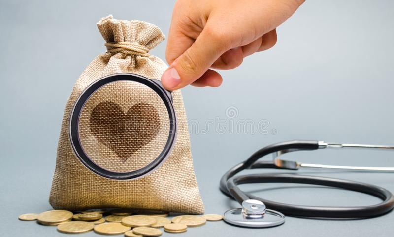 Pengarpåse- och hjärtabild med stetoskopet Begreppet av medicinsk försäkring av liv, familj, hälsa Sjukvård Ackumulationen royaltyfria foton