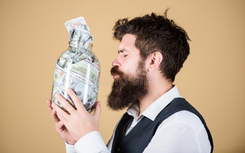 Pengarvän Brutal affärsman som kysser exponeringsglaskruset med pengar Sparande kassapengar för skäggig man i spargrisen Han är g arkivbilder