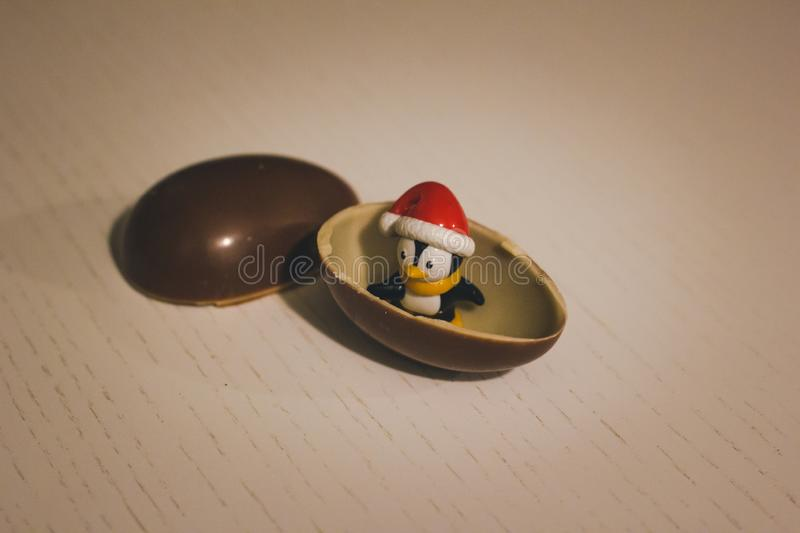 Penguin toy in the chocolate egg. Childhood in my heart. Kinder. Surprise royalty free stock image