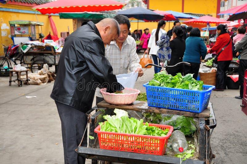 Pengzhou, Κίνα: Farmer που πωλεί τα πράσινα στην αγορά στοκ φωτογραφία με δικαίωμα ελεύθερης χρήσης