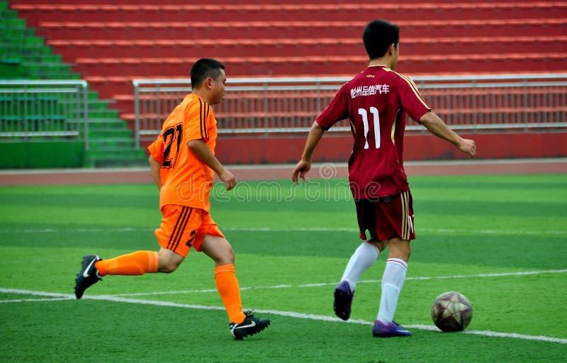 Pengzhou, China: Atletas que jogam o futebol foto de stock royalty free