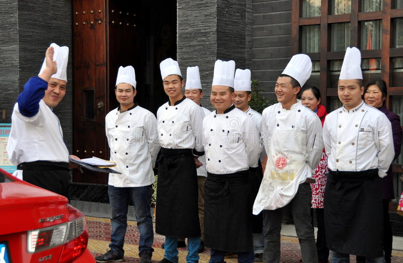 Pengzhou, China: Chefs at Dinner Briefing. Chefs standing in front of their restaurant for pre-dinner briefing from head chef (waving, at left) in Pengzhou royalty free stock photo